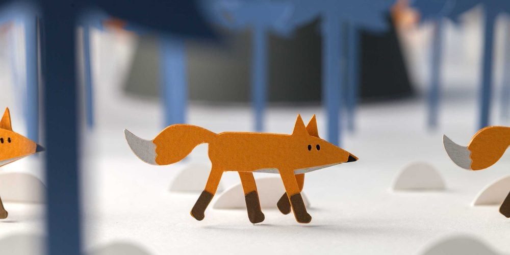 Papercraft fox walking in woods