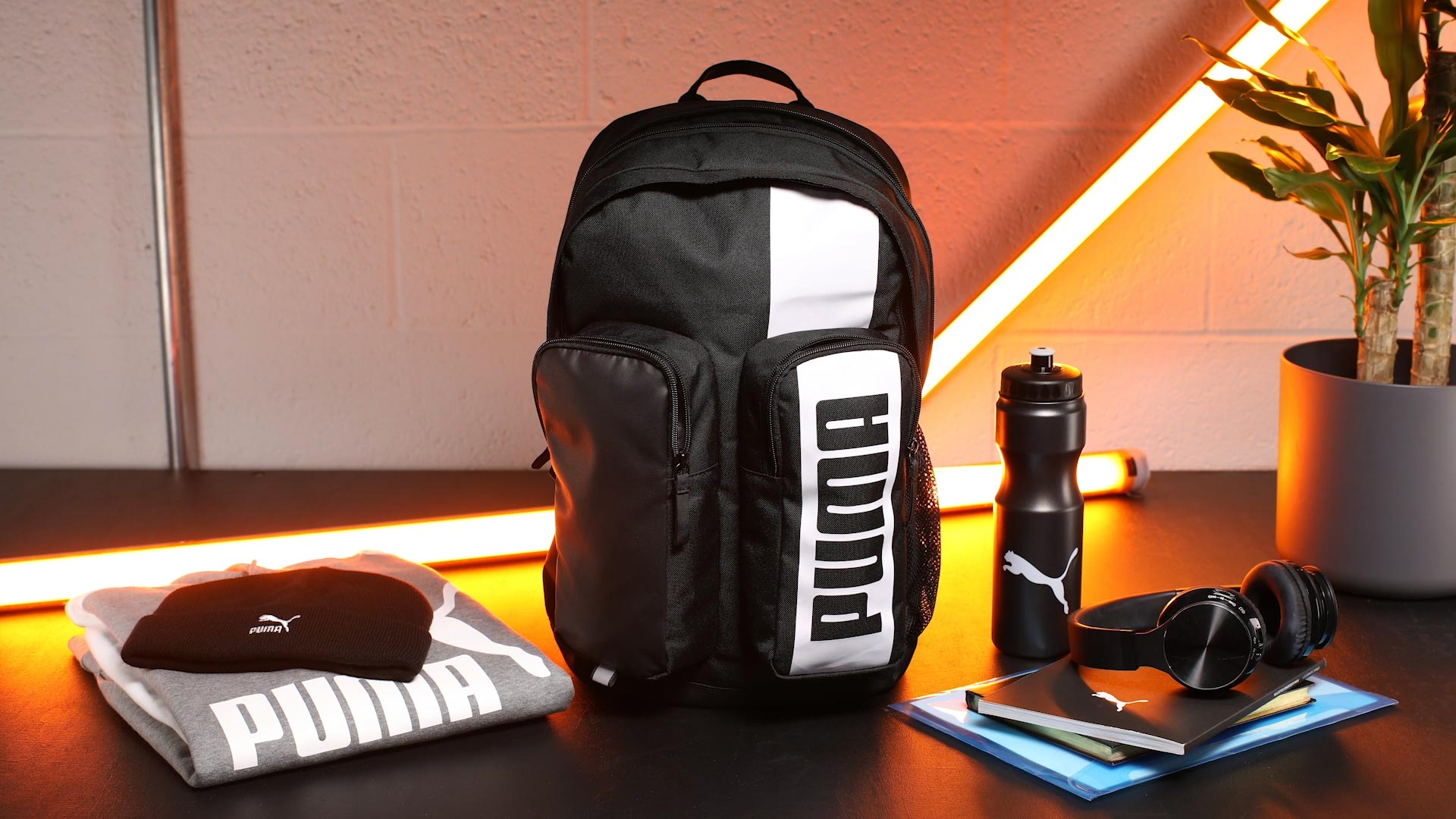 Neatly arranged objects around black Puma back pack stop motion