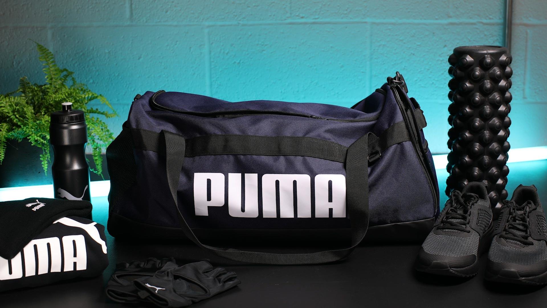 Neatly arranged black objects around Puma sports bag stop motion