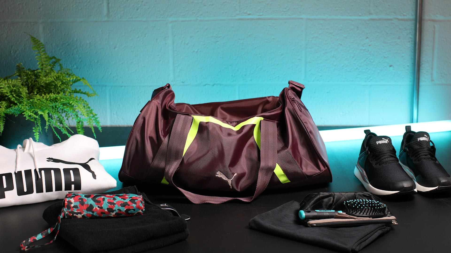 Neatly arranged objects around Puma sports bag stop motion